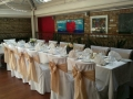 Toffee coloured sashs on white chair covers