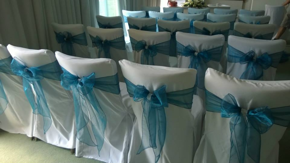 White chair covers with petrol blue sash and sparkle band