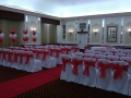 White chair covers with red organza sash